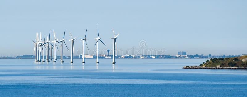 Turbiner för frånlands- vind på kusten av Köpenhamnen i Danmark med flygplatsen i bakgrunden royaltyfri foto