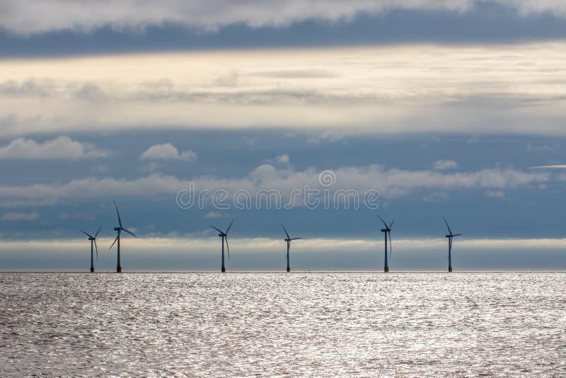 Turbiner för havsbaserade vindkraftverk på havshorisont med molnbakgrund arkivfoton