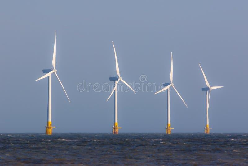 Turbiner för lantgård för frånlands- vind på havshorisont Förnybar ren ener arkivfoto