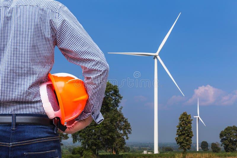 Turbiner för vind för framdel för hjälm för säkerhet för teknikerinnehavguling som frambringar elektricitetskraftverket royaltyfri fotografi