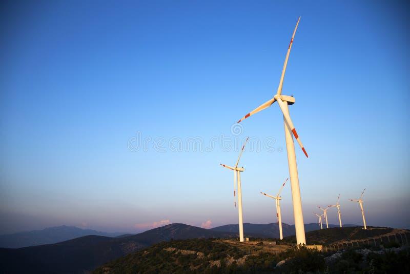 Turbiner för vindenergi är på berget och producerar mest ren elektrisk energi arkivbilder