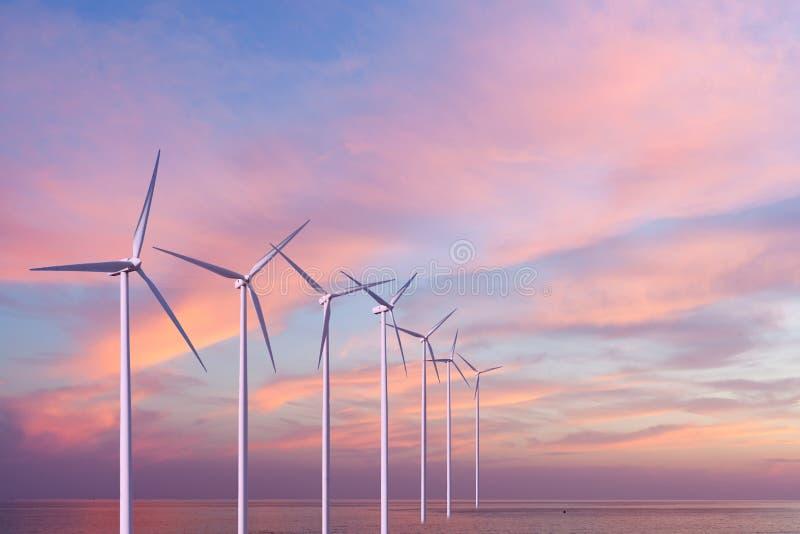 Turbiner för vindgeneratorer i havet på solnedgång royaltyfri fotografi