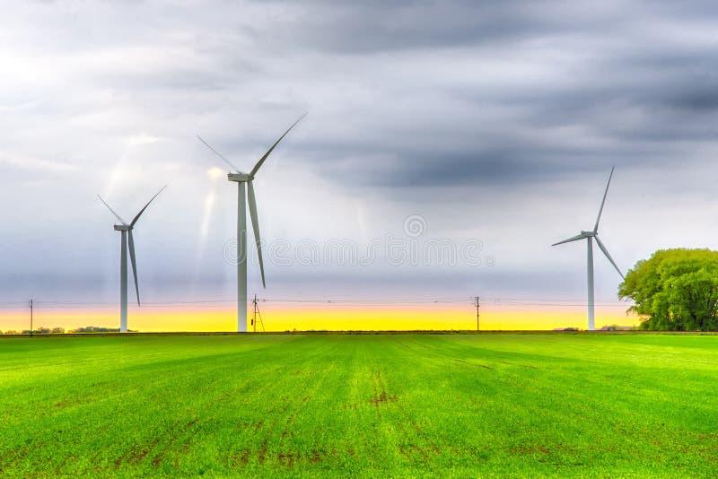 Turbiner för vindkraftväxt på ett grönt fält under himmel med moln på solnedgång Grön energi, förnybara källor, räddningplanet arkivbilder