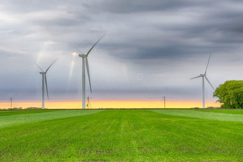 Turbiner för vindkraftväxt på ett grönt fält under himmel med moln på solnedgång Grön energi, förnybara källor, räddningplanet royaltyfri bild