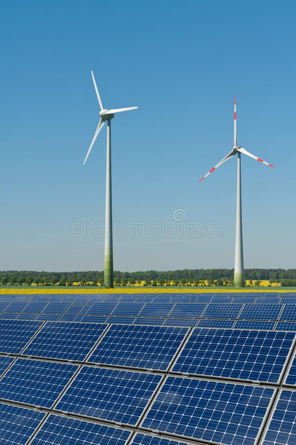 Turbines de vent et panneaux solaires contre une graine de colza photos libres de droits