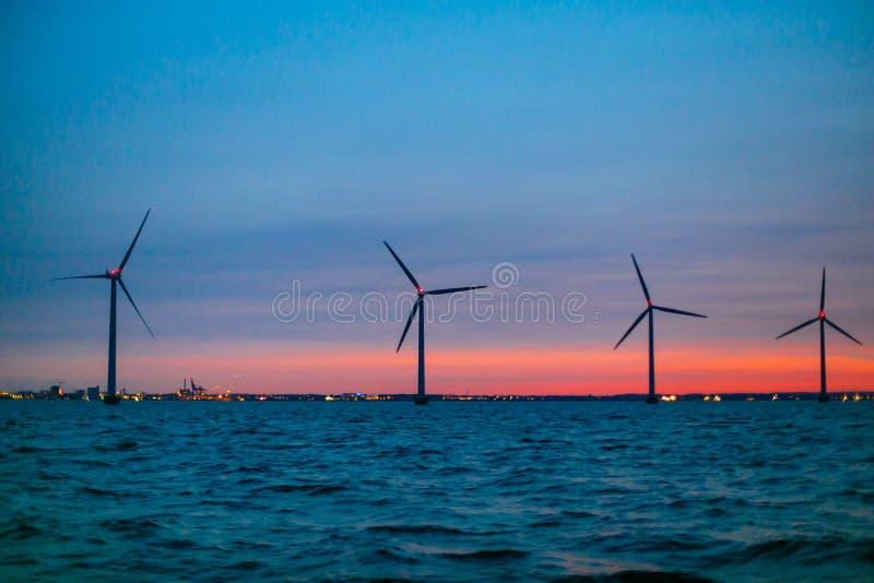 Turbines de vent produisant l'énergie le long du littoral Terres marines images libres de droits