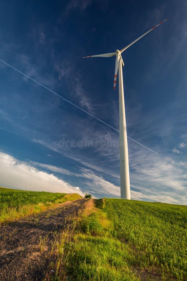 Turbines de vent sur le champ vert et le ciel bleu dans la campagne image libre de droits