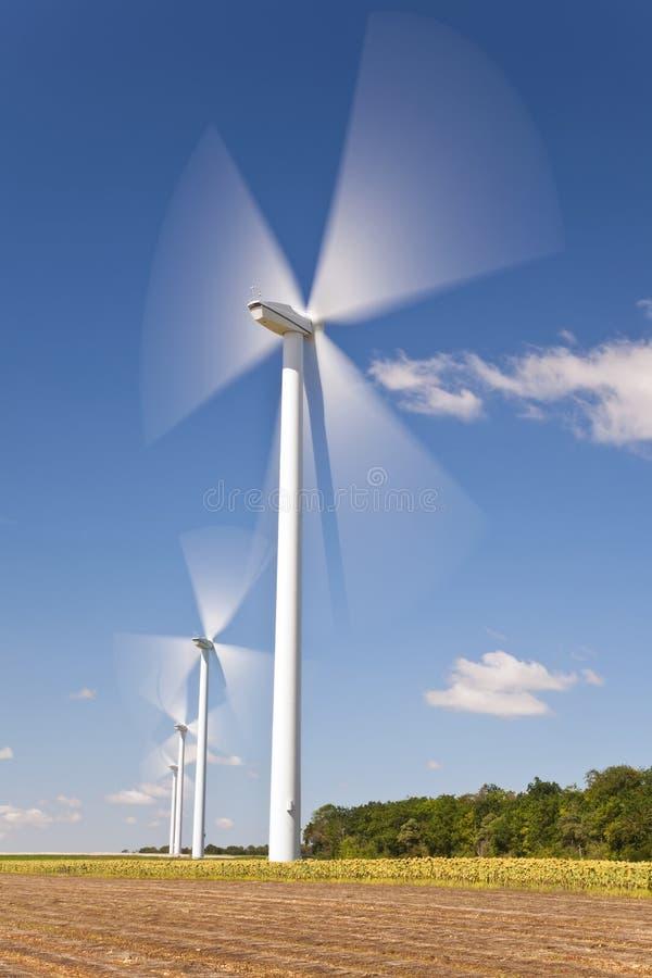 Turbines de vent vertes d'énergie dans le domaine des tournesols photos libres de droits