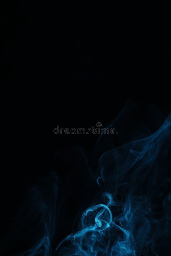turbinio blu di fumo su fondo nero immagini stock