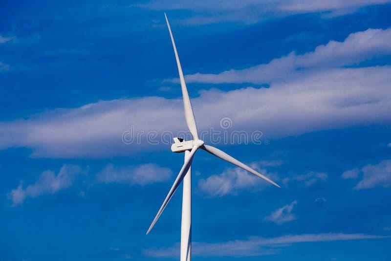Turbinväderkvarnar för utveckling av elektricitet i miljövänlig väg installeras i fält arkivbilder