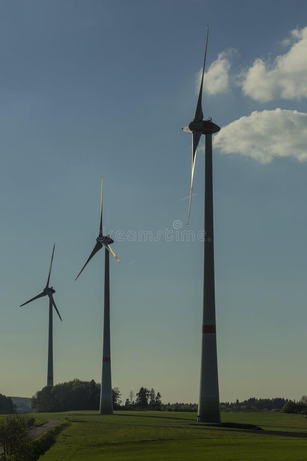 Turbiny wiatrowe na zielonym polu ze ścieżką Ekologiczna, odnawialna i zrównoważona alternatywa dla tradycyjnych źródeł fotografia stock