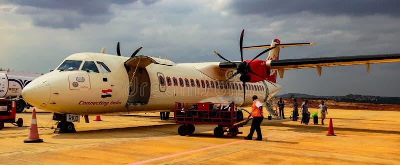 Turbo-Stützenflugzeug sitzt auf Asphaltladen Passagieren und luggag stockfotografie