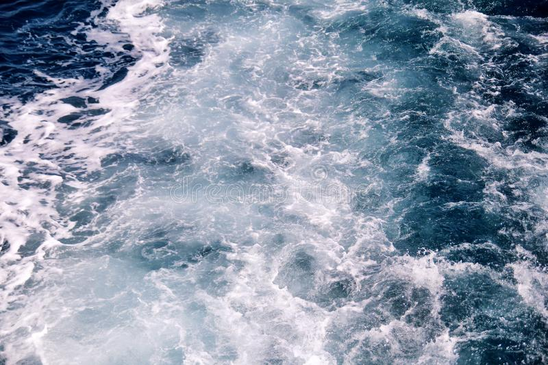Turbulence made by foam of sea water from a high-speed yacht on surface of sea. Blue sea waves with lot of sea foam. Surface of sea with waves, splash, foam royalty free stock photography