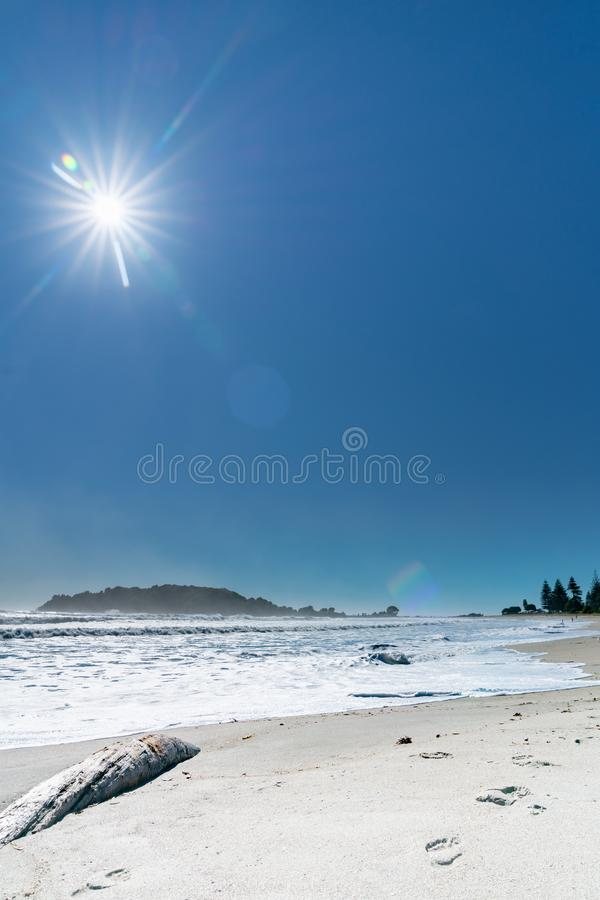 Turbulent sea during strong ocean surge. Footprints in sand past log with turbulent sea during strong ocean surge with Moturiki Island at end of beach royalty free stock photo