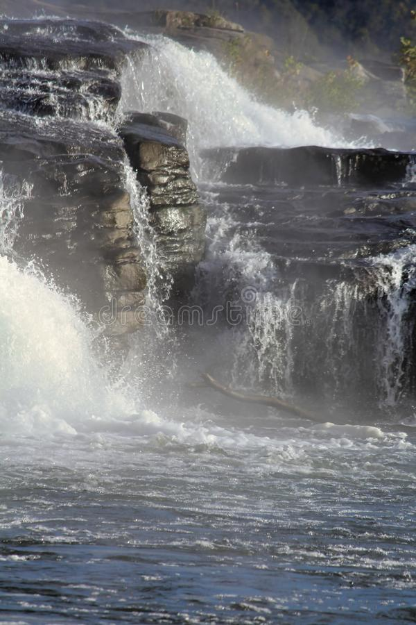 Turbulent water cascading over the weathered rocks stock images