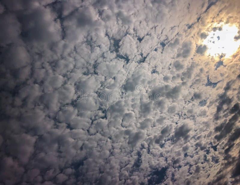 Turbulenta himlar med solen som igenom kikar arkivfoto