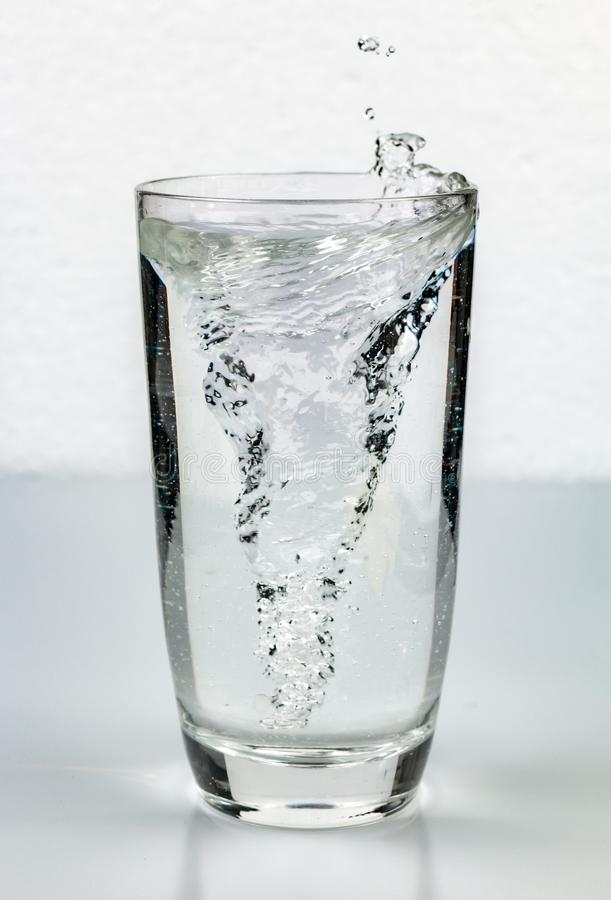 Turbulenzstrudel im Glas Wasser lizenzfreies stockbild