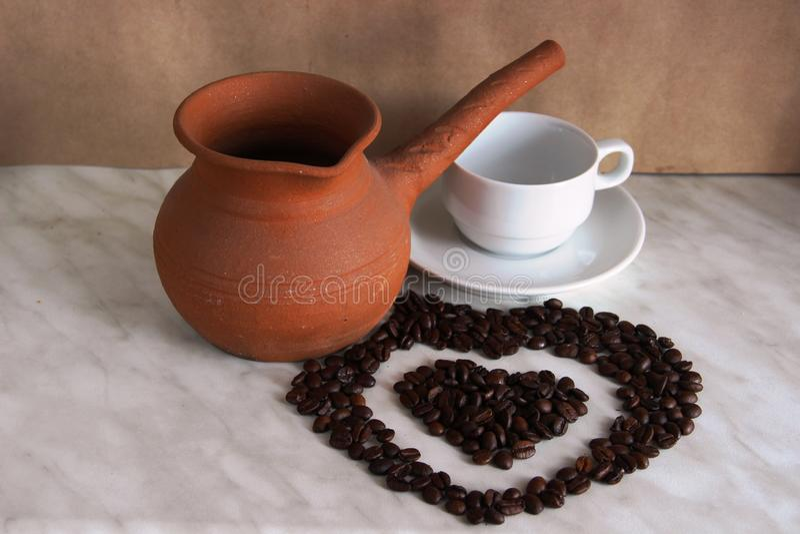 Turc d'argile de Brown pour faire cuire le caf?, la tasse et soucoupe blanche et les grains de caf? r?tis sous forme de coeur image libre de droits