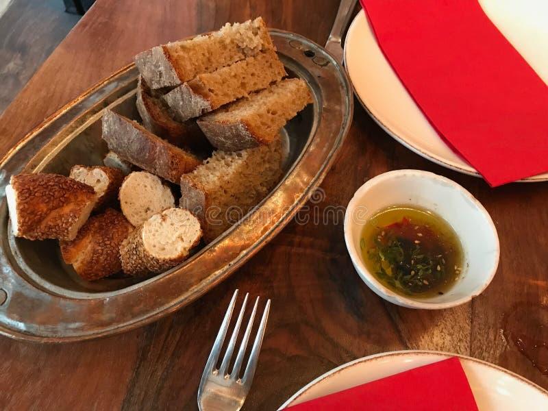 Turc Olive Oil avec les graines de noyau, le pain frais et les tranches de bagel au Tableau de petit déjeuner photo libre de droits