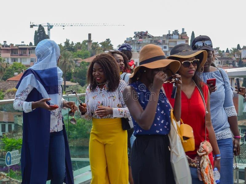 Turcja, Antalya, Maj 10, 2018 Grupa młode Afrykańskie kobiety w jaskrawym odziewa na viewing platformie w starym mieście sprawdza zdjęcia royalty free