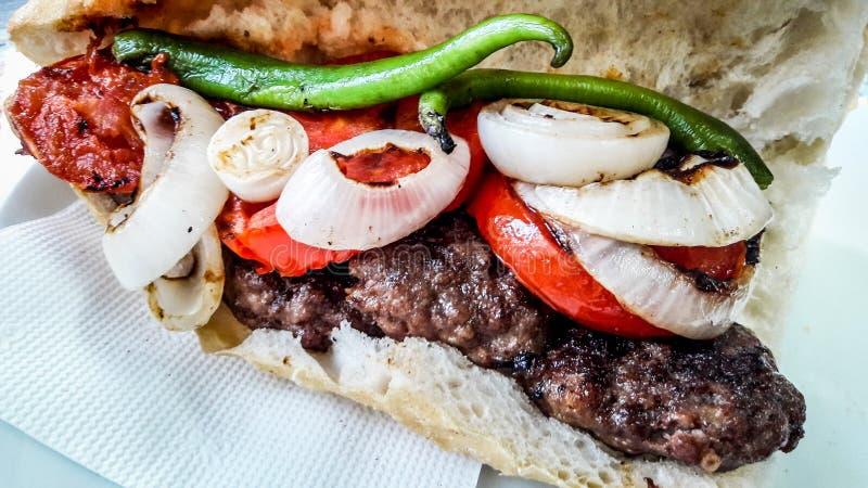 Turco Kofte Ekmek/bocadillo de la albóndiga con los tomates, la cebolla y la pimienta verde fotografía de archivo libre de regalías