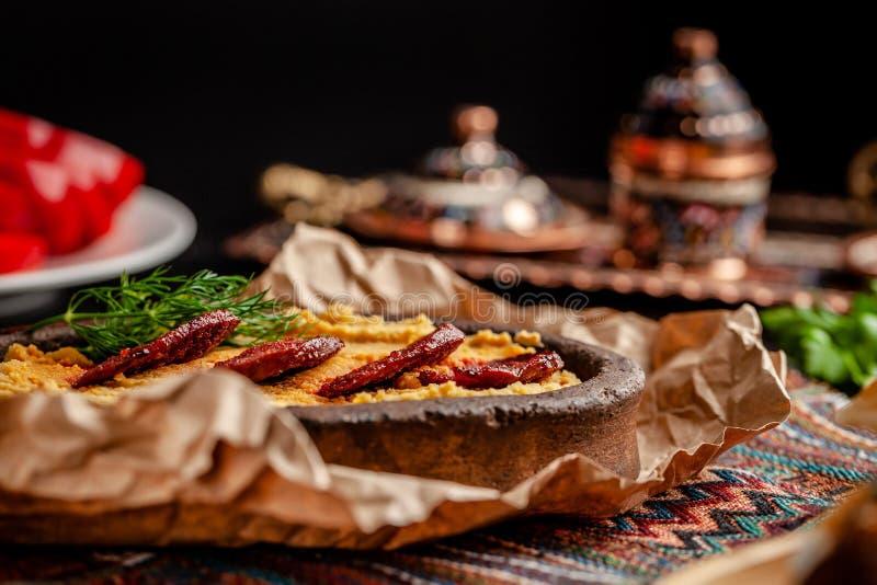 Turco tradicional, cocina árabe Hummus con la salchicha del salami, en una placa de la arcilla, con el pergamino en una tabla de  foto de archivo libre de regalías