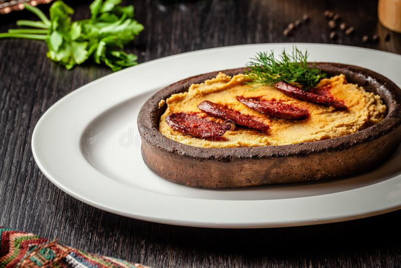 Turco tradicional, cocina árabe Hummus con la salchicha del salami, en una placa de la arcilla, en una tabla de madera En una pla imágenes de archivo libres de regalías
