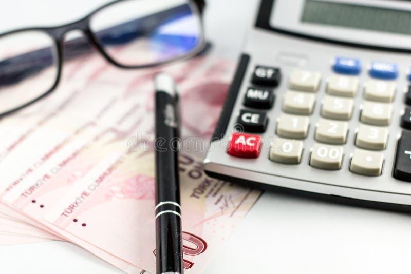 Tureccy banknoty, szkła, pióro i kalkulator na z białym tłem, fotografia stock