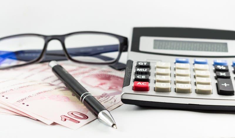 Tureccy banknoty, szkła, pióro i kalkulator z białym tłem, zdjęcie stock