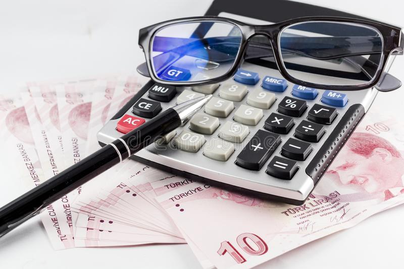 Tureccy banknoty, szkła, pióro i kalkulator z białym tłem, obrazy stock