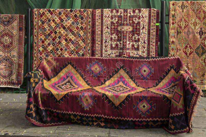 Tureccy dywany wystawiali na ulicie niektóre obwieszenie i jeden drapował nad siedzeniem z kwiatów płatkami od drzew spadać wokoł zdjęcia stock