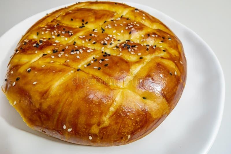 Turecczyzny Ramadan chleb, pita chleb na bielu talerzu z sezamami i czerni ziarna, fotografia royalty free