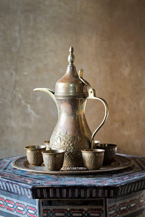 Turecka kawa ustawiająca: Osmański ozdobny kawowy garnek i małe ozdobne filiżanki na dekorującej tacy i dekorującym języka arabsk obraz stock