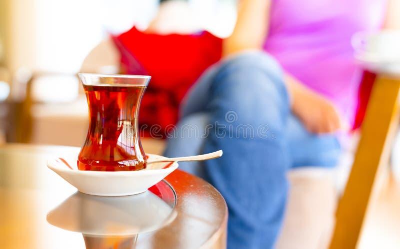 Turecka kobieta pije tradycyjnej Tureckiej herbaty od ince belli bardak fotografia stock