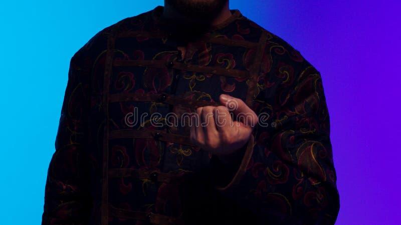 Turecki brodaty młody człowiek w krajowy kostiumowym otwierający wolno jego palmy i pokazywać czerń, round moneta zapas Turecki m zdjęcia stock