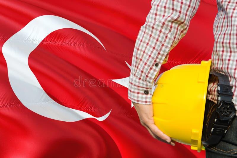 Turecki inżynier trzyma żółtego zbawczego hełm z machać Turcja chorągwianego tło Budowy i budynku poj?cie obraz royalty free