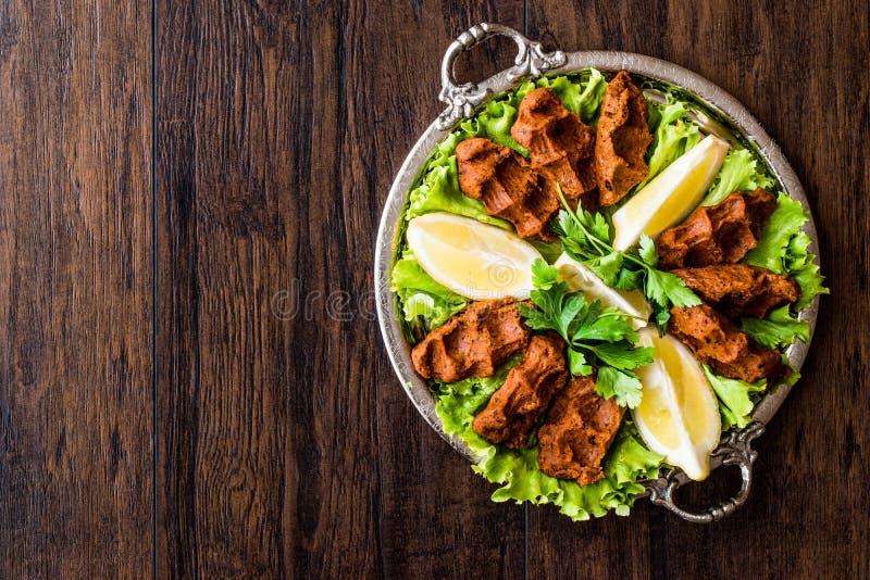 Turecki Karmowy Cig Kofte z cytryną, sałatą i pietruszką na srebnej tacy, zdjęcie royalty free