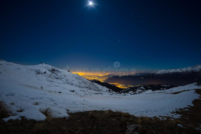 Turin city lights, night view from snow covered Alps by moonlight. Moon and Orion constellation, clear sky. Italy. royalty free stock photos