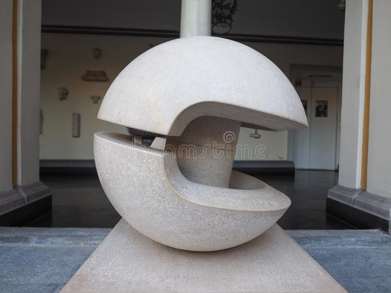 Gio Pomodoro sculpture in Turin. TURIN, ITALY - CIRCA AUGUST 2017: Stone sculpture entitled Guscio (meaning Shell) by artist Gio Pomodoro outside Accorsi Ometto stock image