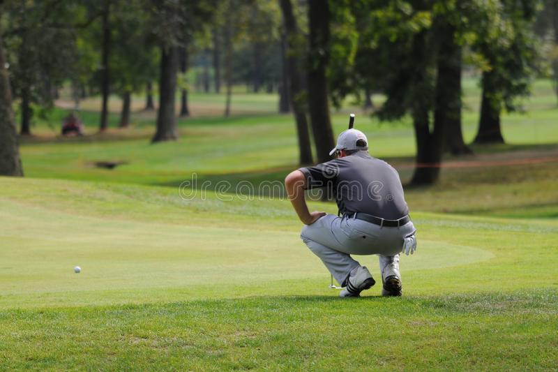 Turin Italy circa September Unknown golf player alone concentrate seek the right line squatted on green. Turin Italy circa September 2016 Unknown golf player stock photography