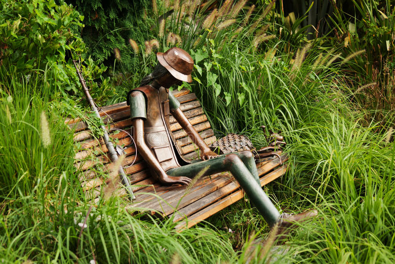 TURIN, ITALY - JULY 12, 2016: Urban sculpture by Rodolfo Marasciuolo of a fisherman with fishing rod, basket and cat on a bench o royalty free stock photos