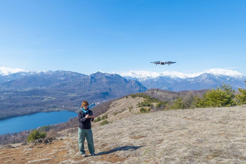 Woman flying drone outdoors with remote control. One person in scenic landscape driving drone filming photographing snowcapped mou stock images
