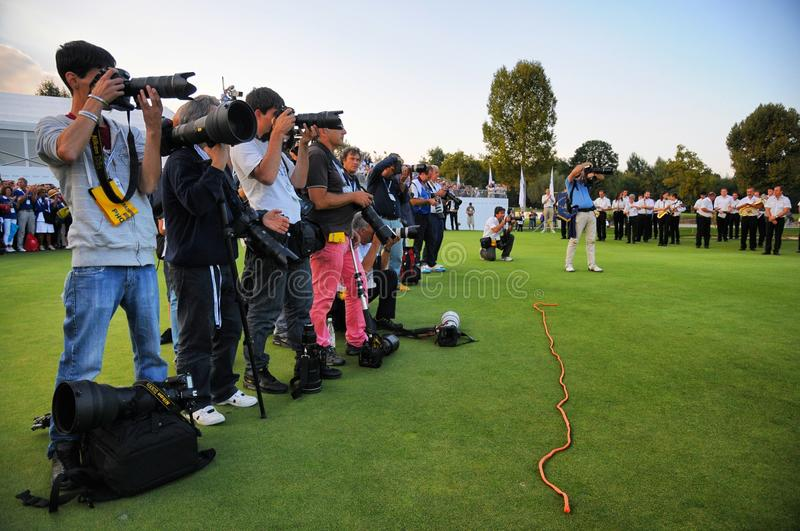 Professional photographers working during a sport event behind a red rope line limit on grass stock photography