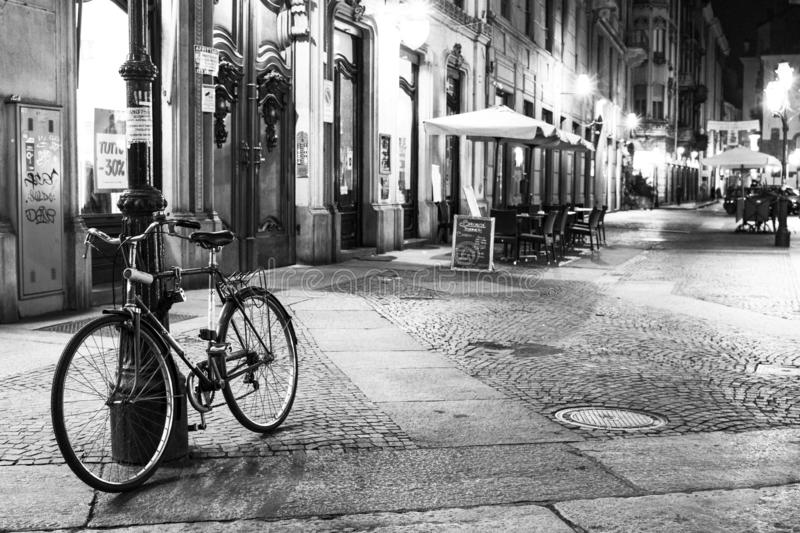 Turin, Piedmont, Italy night view of via mercanti. In black and white with a bicycle leaning against a street lamp royalty free stock images