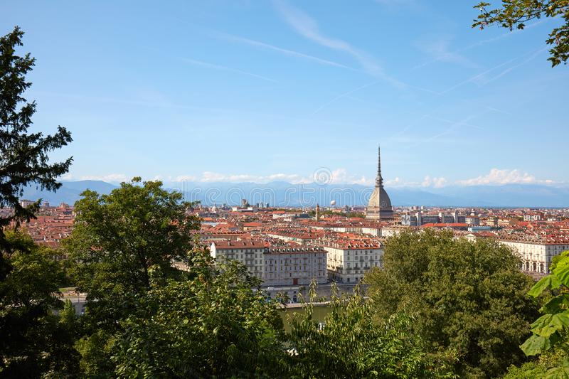 Turin skyline view and Mole Antonelliana tower seen from the hill with vegetation in a sunny summer day in Italy. Turin skyline view and Mole Antonelliana tower royalty free stock photography