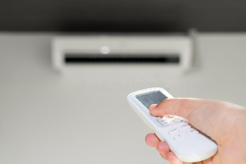 Turing an, die Klimaanlage durch Fernbedienung abstellend lizenzfreie stockfotos