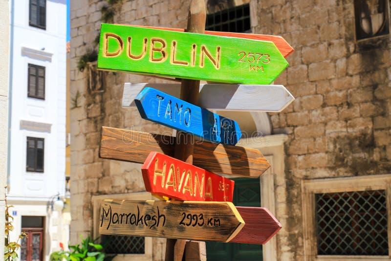 Turism- och loppbegrepp Riktningar och avstånd för färgrikt trävägmärke peka till städer och länder - havannacigarr, Dublin, royaltyfri fotografi