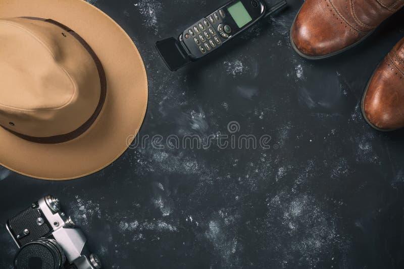 Turism- och loppbegrepp Tappningfilmkamera, bruntskor, fedorahatt och gammal mobiltelefon på svart stenbakgrund Fri spac royaltyfri fotografi
