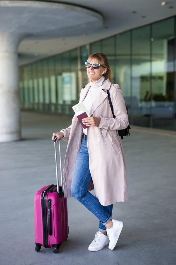 Turism- och loppbegrepp - ung kvinnlig turist med väntande logi för resväska och för pass i flygplats eller station arkivfoto