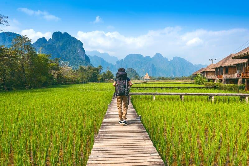 Turismo com a trouxa que anda no trajeto de madeira, vieng de Vang em Laos imagem de stock